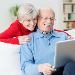 glückliches senioren-paar schaut auf laptop